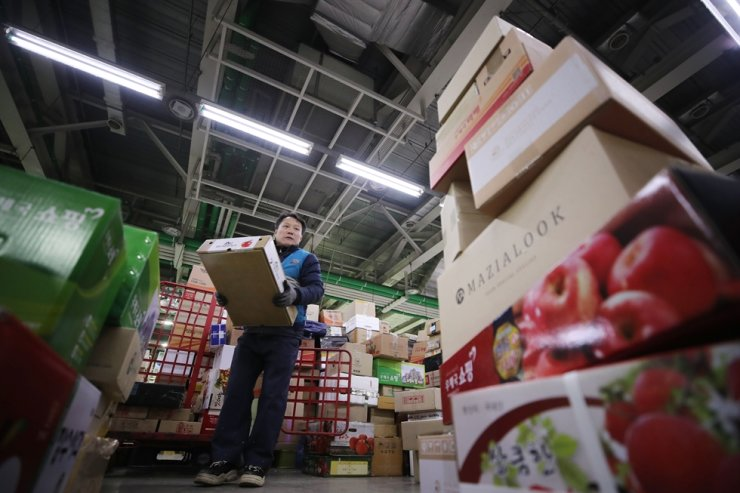 A Korea Post worker sorts out boxes of parcels to deliver at a parcel depot handling the eastern Seoul zone in the city's Gwangjin District on Jan. 14, 2020. Yonhap