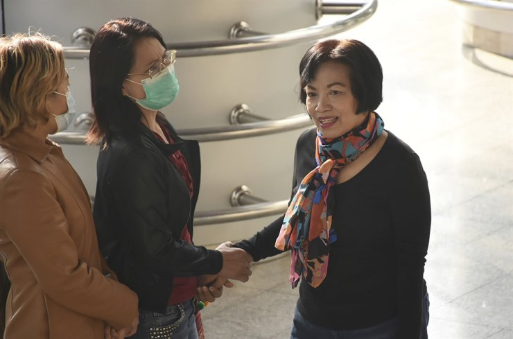 A woman identified only by her first name Anchan, right, shakes hand with a friend as she arrives at the Bangkok Criminal Court in Bangkok, Thailand, Tuesday. A court in Thailand on Tuesday sentenced a retired civil servant to a record 43.5 years in prison for insulting the monarchy by posting audio clips online of comments critical of the royal institution. / AP-Yonhap