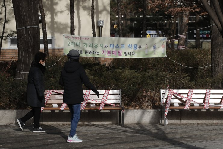 Visitors wearing face masks as a precaution against the coronavirus walk past benches taped for social distancing at a park in Seoul, Thursday, Jan. 14, 2021. AP