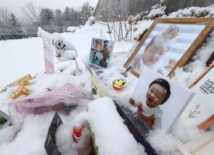 Photos of Jung-in, a 16-month-old girl who died after being abused by her adoptive parents, sit in front of her grave at a cemetery in Yangpyeong, Gyeonggi Province, Jan. 13. Yonhap