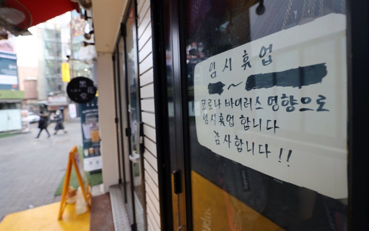 A notice announcing a shop is closed because of the prolonged COVID-19 pandemic is posted in Myeong-dong, central Seoul, Sunday. The government decided to maintain the social distancing at the current Level 2.5 for the Seoul metropolitan area despite deepening difficulties facing small business owners, amid the continued spread of the coronavirus. / Yonhap