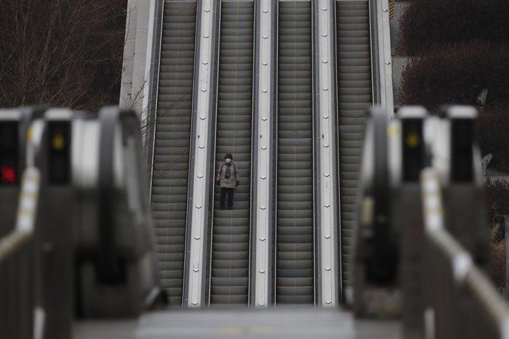 A woman wearing a face mask as a precaution against the coronavirus takes an escalator down in Seoul, Jan. 21. AP