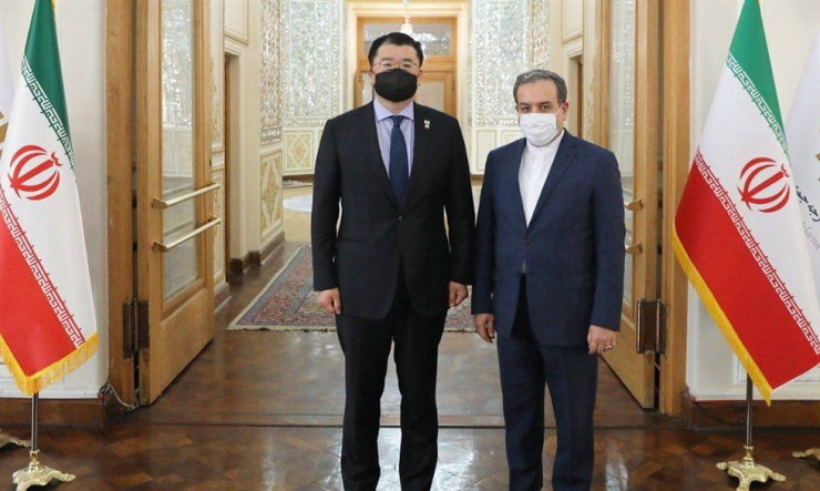 A handout photo made available by the Iranian Foreign Ministry shows Iranian Deputy Foreign Minister Abbas Araghchi, right, greets his Korean counterpart Choi Jon-kun during a meeting in Tehran, Jan. 10, 2021. EPA