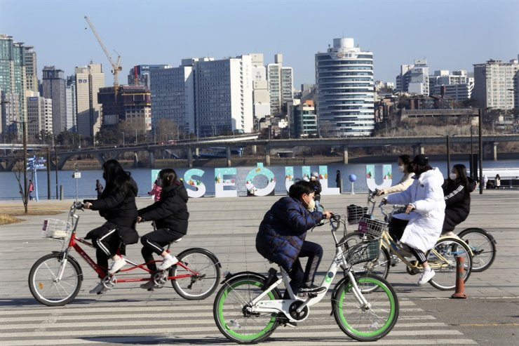 Young people wearing face masks to help protect against the spread of the coronavirus ride bicycles at a park in Seoul, Sunday, Jan. 24, 2021. AP