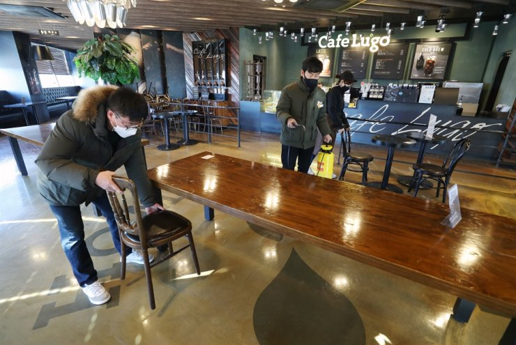 Cafe workers in Daegu spray disinfectant and organize chairs and tables, Sunday, as cafes are allowed to offer dine-in services beginning from Monday, after the government decided to ease restrictions on businesses hit by COVID-19. / Yonhap