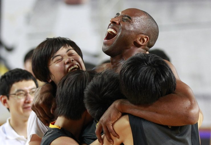 Los Angeles Lakers Kobe Bryant embraces Korean students in his basketball clinic for youth in Seoul, Thursday, July 14, 2011. Jan. 26, 2021, marks the anniversary of the helicopter crash that killed the NBA star. AP
