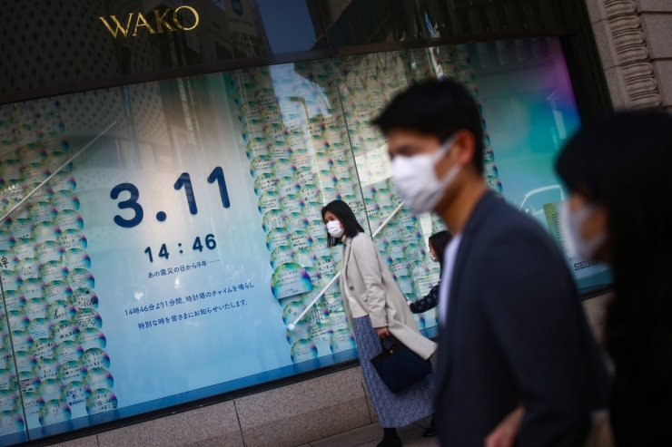 People wearing masks are seen next to a board with messages mourning the victims of the March 11, 2011, earthquake and tsunami disaster that killed thousands and set off a nuclear crisis, at Ginza shopping district in Tokyo, March 11, 2020. Reuters