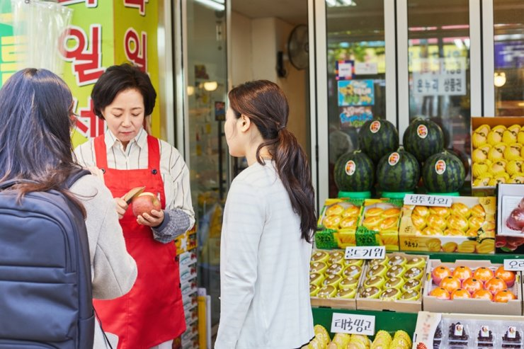 A fruit store owner talks with customers in this file photo. Getty Images Bank