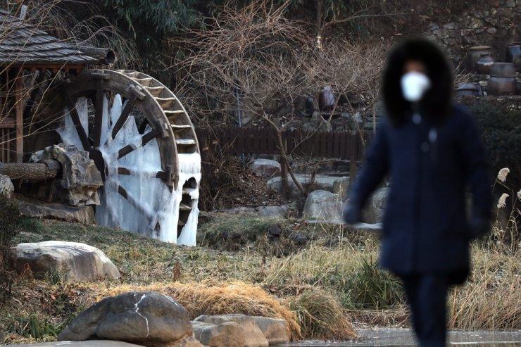 A woman walks past the frozen waterwheel near Hongje Stream in Seoul, Wednesday. Yonhap