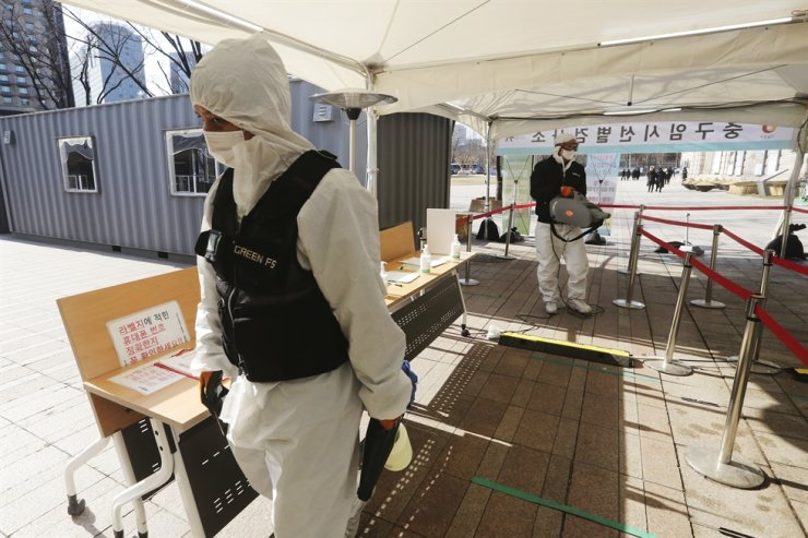 A man wearing protective suits sprays disinfectant as a precaution against the coronavirus during lunch time at a makeshift clinic in Seoul, Wednesday, Jan. 20, 2021. AP