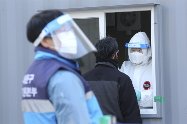 A medical worker in a booth takes nasal samples from a man at a coronavirus testing site in Seoul, Jan. 19, 2021. AP