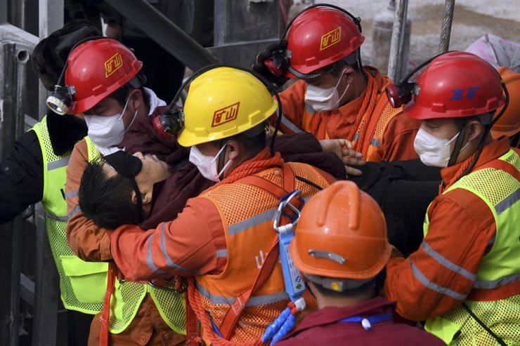 In this photo released by Xinhua News Agency, rescuers carry a miner who was trapped in a mine to an ambulance in Qixia City in east China's Shandong Province, Jan. 24 (local time). Eleven workers trapped for two weeks by an explosion. / Xinhua-Yonhap