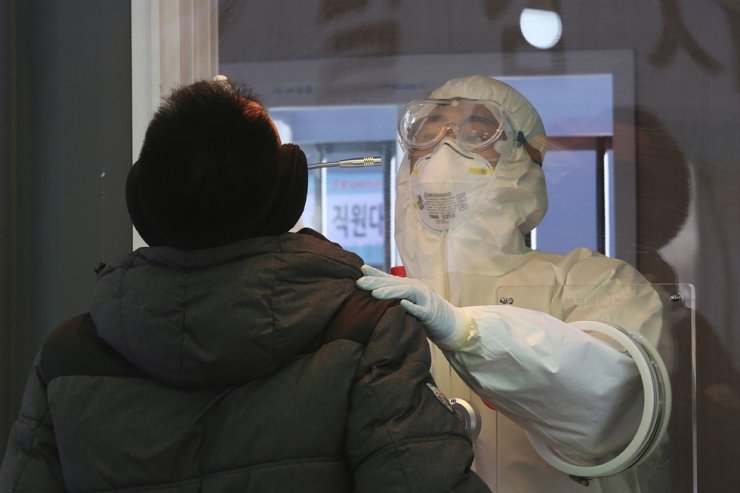 A medical worker in a booth takes a sample from a man at a coronavirus testing site in Seoul, Wednesday, Jan. 6, 2021. AP