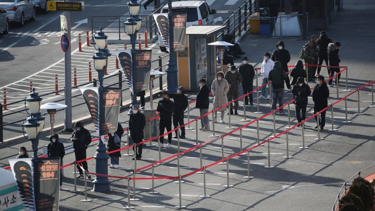 Citizens wait in line to go through COVID-19 testing at a temporary testing facility in front of Seoul Station, Sunday. / Yonhap