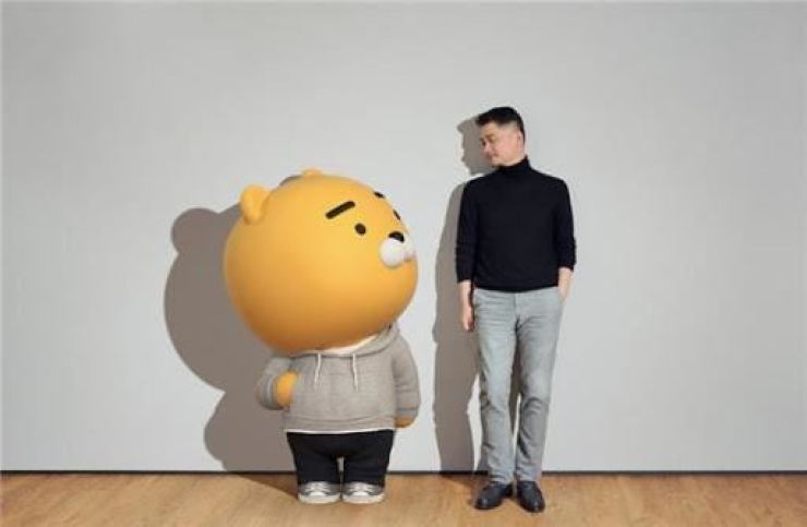 Kakao founder and Chairman Kim Beom-su, right, poses with the company's Ryan bear. / Courtesy of Kakao