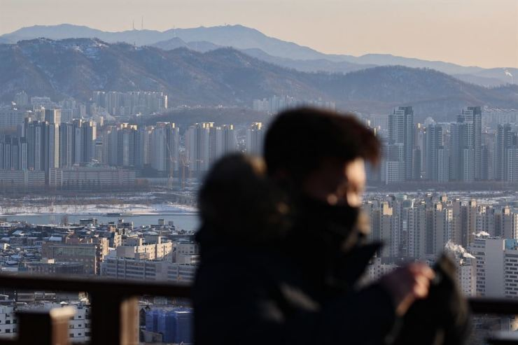 Apartment complexes are seen behind a visitor to N Seoul Tower on Jan. 7. Yonhap