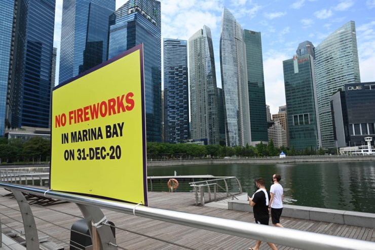 People walk past a signboard displaying a message stating that there will be no fireworks in Marina Bay in Singapore on Dec. 25, 2020. AFP