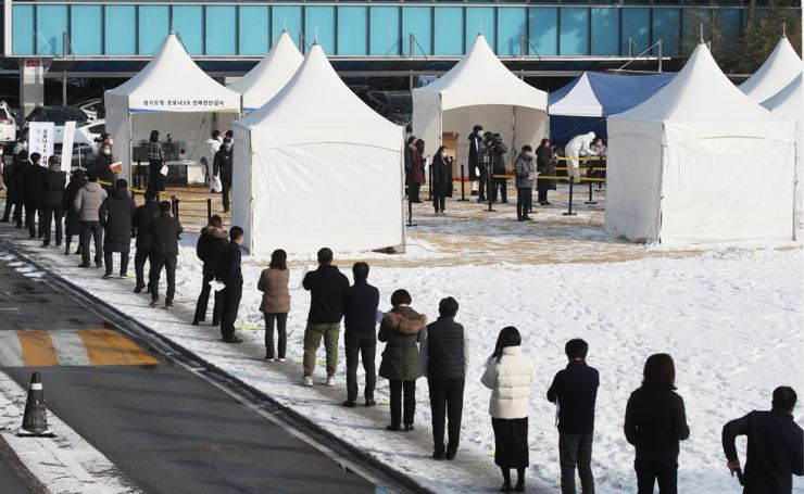Public servants of Gyeonggi Provincial Government and its affiliates line up for coronavirus tests at a makeshift testing center set up at the provincial government building compound in Suwon, Wednesday. Yonhap