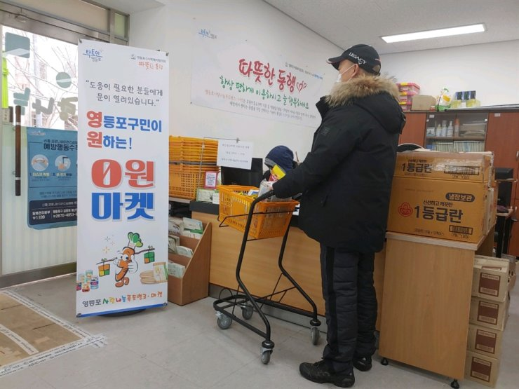 A resident picks up food and daily necessities at Yeong Won Market in Yeongdeungpo District Office building in Seoul. The district office runs the market where needy residents can receive the necessities for free. Courtesy of Yeoungdeungpo District Office