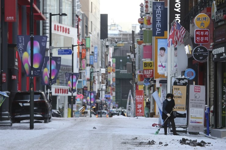 A woman wearing a face mask as a precaution against the coronavirus clears snow at a shopping street in Seoul, Jan. 7. AP-Yonhap