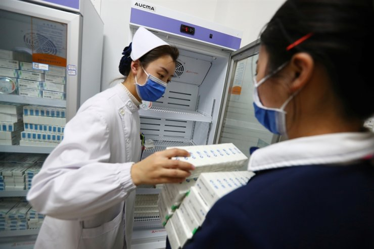 A nurse carries boxes of the coronavirus vaccine developed by Sinopharm at a hospital in Nanchang, Jiangxi province, China, Jan. 6, 2021. Seychelles said it has started vaccinating its population against the disease with does from the Chinese company. Reuters