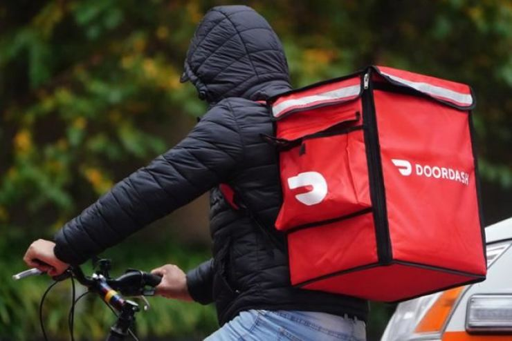 A delivery person for DoorDash rides his bike in the rain during the coronavirus pandemic in the Manhattan borough of New York City, Nov. 13. / REUTERS-Yonhap