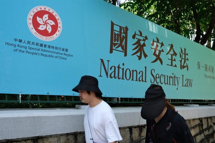 Pedestrians walk past a government public notice banner for the National Security Law in Hong Kong in this file photo taken on July 15, 2020. / AFP-Yonhap