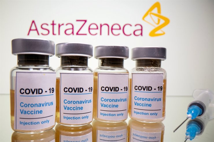 Vials with a sticker reading, 'COVID-19 / Coronavirus vaccine / Injection only' and a medical syringe are seen in front of a displayed AstraZeneca logo in this illustration taken on Oct. 31, 2020. Reuters