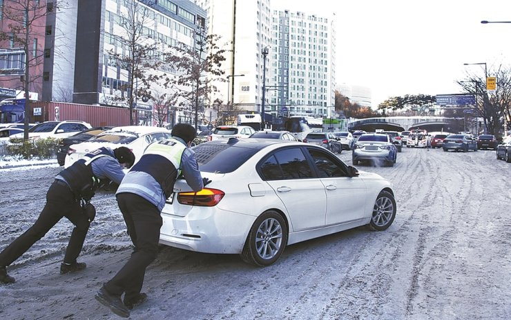 Police officers push a car on a snow-covered road in Suwon, Gyeonggi Province, Thursday. Heavy snow combined with a cold snap the previous night created traffic chaos for commuters in Seoul and the surrounding metropolitan area. Yonhap