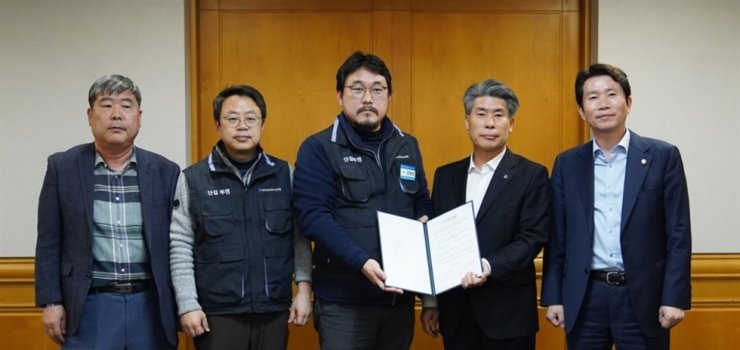 Industrial Bank of Korea CEO Yoon Jong-won, second from right, poses with Kim Hyung-sun, center, the lender's labor union chief, at the headquarters of the Korea Federation of Banks in Seoul, on Jan. 27 last year. Yonhap