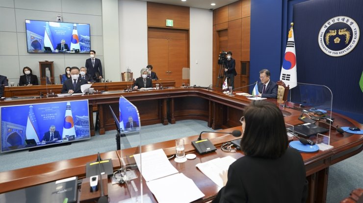 President Moon Jae-in listens to Uzbek President Shavkat Mirziyoyev at Cheong Wa Dae in Seoul during their virtual summit, Thursday. Yonhap
