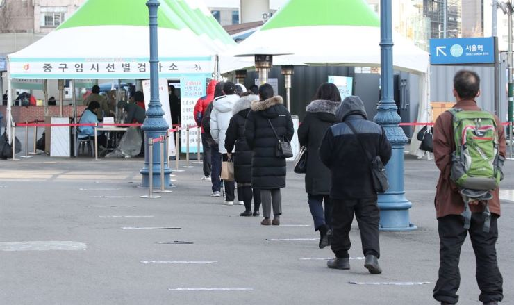 People stand in line to get COVID-19 tests at a temporary screening station in front of Seoul Station, Wednesday. Yonhap