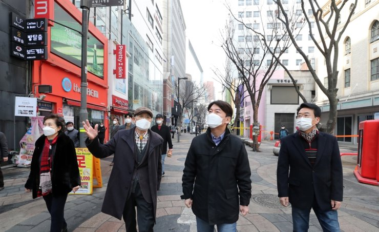President of minor People's Party and one of the upcoming Seoul mayoral election runners Ahn Cheol-soo, second from right, on Feb. 14 visits popular shopping district Myeongdong in Seoul's Jung District that has been hit hard by COVID-19's economic impact, with many restaurants and other stores forced to close. Yonhap