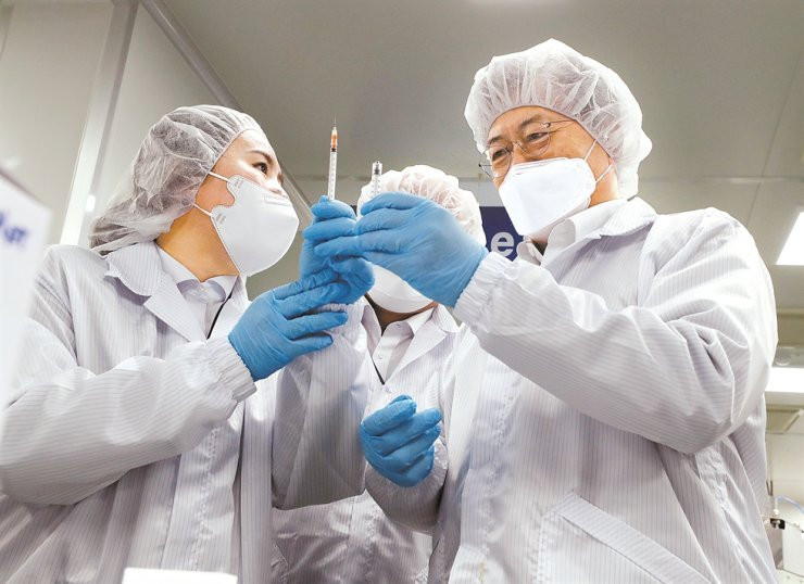 President Moon Jae-in inspects a low dead-space (LDS) syringe during his visit to a plant of Poonglim Pharmatech, the manufacturer of the medical device, in Gunsan, North Jeolla Province, Thursday. The syringe, to be used for COVID-19 vaccinations, has been approved by the U.S. Food and Drug Administration (FDA). / Joint press corps