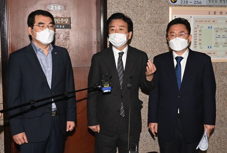 Rep. Noh Woong-rae, center, the leader of the ruling Democratic Party of Korea's taskforce team for media reform, talks to reporters after a meeting at the National Assembly, Tuesday. Noh said they decided to seek the revision of a law to force media to pay punitive damages for victims of 'fake news.' Yonhap