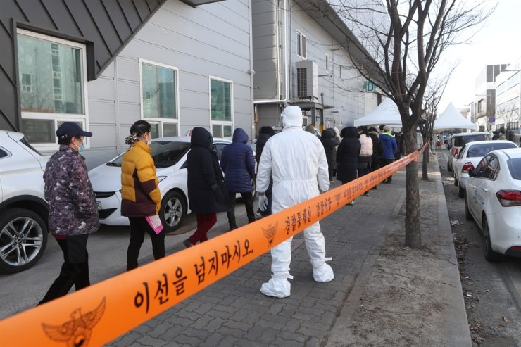 People stand in line for COVID-19 testing at a temporary screening station set up in an industrial complex in Namyangju, Gyeonggi Province, Wednesday. Yonhap