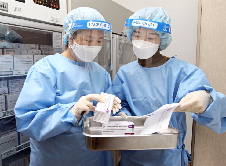 Medical staff examine AstraZeneca's coronavirus vaccines at a public health center in Dongjak District, Seoul, Thursday, ahead of the start of mass vaccinations scheduled for Friday. Yonhap