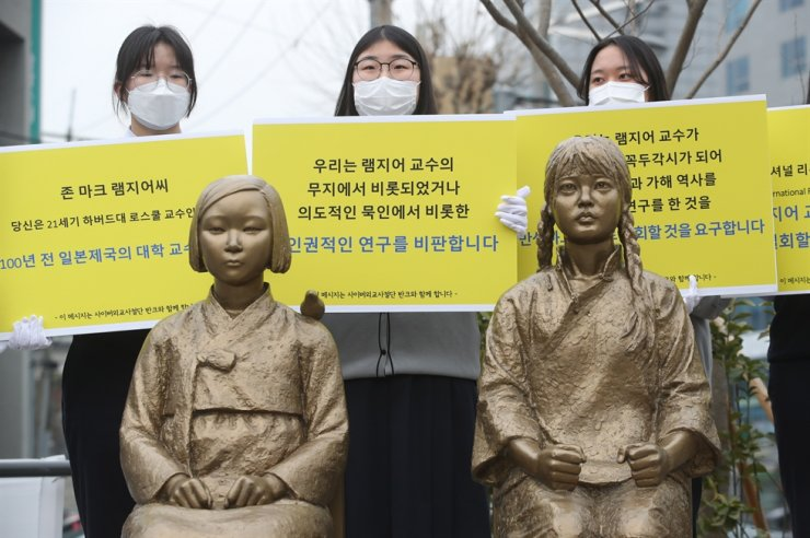 Students of Gyeseong High School denounce Harvard Law School Professor Mark Ramseyer's paper on wartime sex slavery during a rally in Seoul behind statues symbolizing Korean and Chinese sex slaves, Thursday. Yonhap