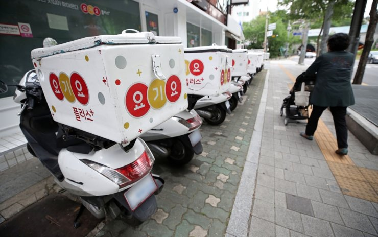 Scooters for delivering orders placed on Yogiyo, the No. 1 food delivery service, are parked in front of its office in Seoul last June. / Yonhap