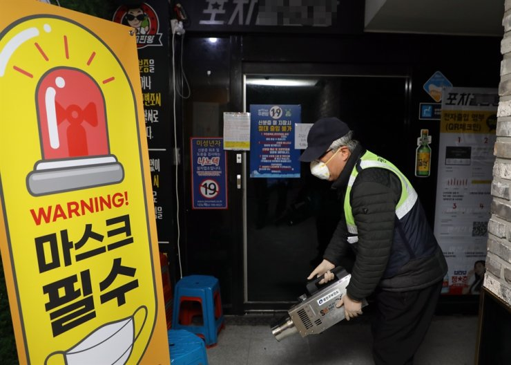 An official from Gwangjin-gu Office disinfects a restaurant operated as a de facto entertainment establishment, Wednesday, following mass infections there. / Yonhap