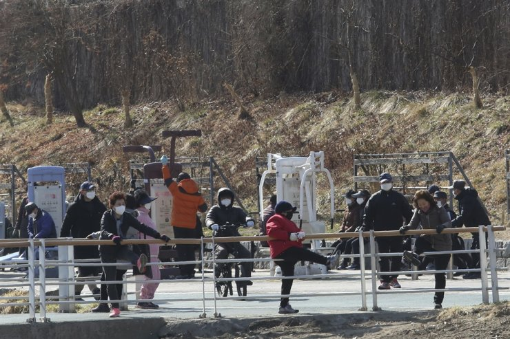 People wearing face masks as a precaution against the coronavirus stretch at a park in Seoul, Tuesday, Feb. 23, 2021. AP
