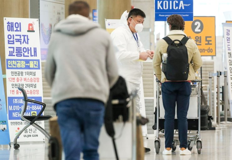 Air travelers who arrived at Incheon International Airport on Feb. 24 go through a medical worker's questioning before heading for public transportation. Yonhap