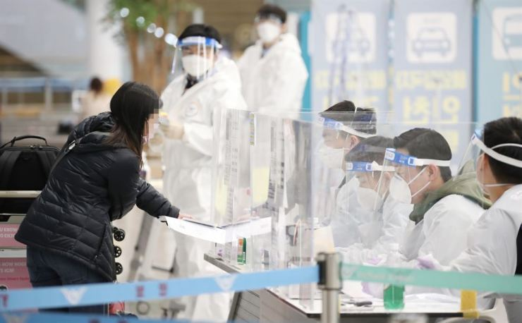 A woman submits documents to quarantine officials at Incheon International Airport, Wednesday. Yonhap