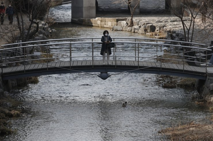 A woman wearing a face mask as a precaution against the coronavirus, holds her smartphone at Cheonggye stream in Seoul, Sunday, Feb. 21, 2021. AP