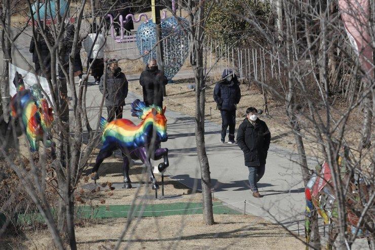Visitors wearing face masks as a precaution against the coronavirus walk at a park in Seoul, Tuesday, Feb. 2, 2021. AP