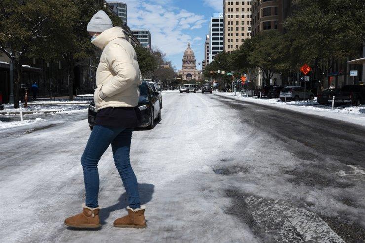 A woman walks across the snow covered street near the Texas state capitol Tuesday, Feb. 16, 2021, in Austin, Texas. AP