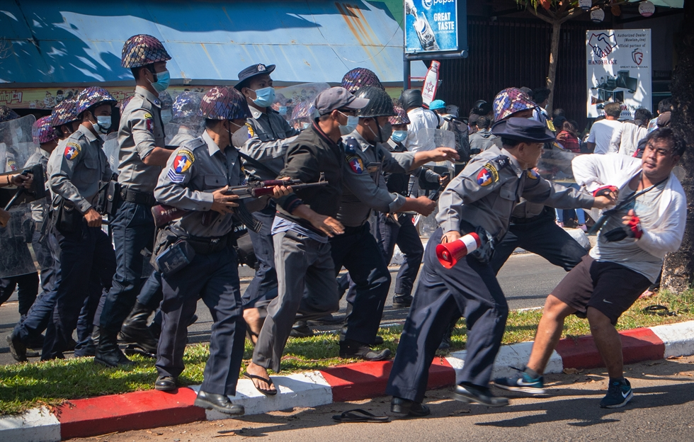 Protesters flashing three fingered salutes and holding an image with an X mark on a photo of Myanmar Commander-in-Chief Senior General Min Aung Hlaing face rows of riot police in Naypyitaw, Myanmar, Feb. 8, after last week's military coup. AP