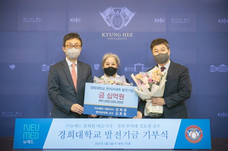 Neumed CEO Kang Hee-won, center, poses with Kyung Hee University President Hahn Kyun-tae, left, and Professor Kim Ho-cheol of Kyung Hee University's College of Korean Medicine during a donation ceremony at the school, Wednesday. Courtesy of Neumed