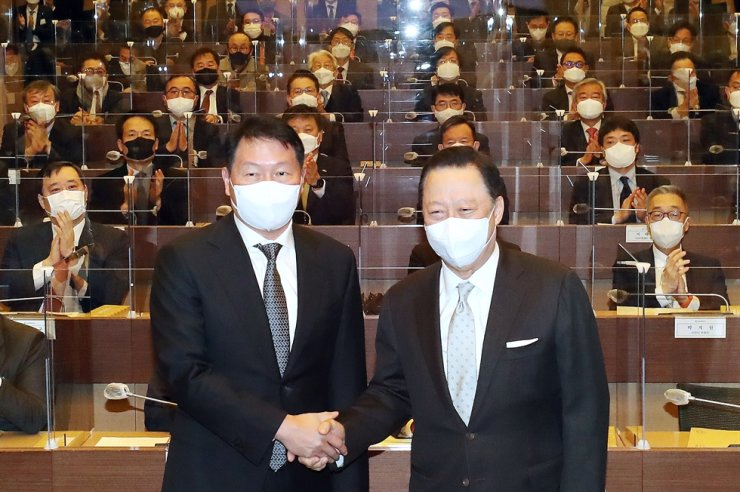 SK Group Chairman Chey Tae-won, left, shakes hands with outgoing Korea Chamber of Commerce and Industries (KCCI) Chairman Park Yong-maan during a general meeting of the Seoul Chamber of Commerce and Industries in Seoul, Tuesday. Chey was appointed as the chairman of the Seoul chamber and will succeed Park as KCCI chairman in March. Yonhap
