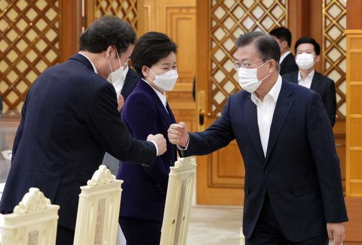 President Moon Jae-in, right, greets Lee Nak-yon, chairman of the ruling Democratic Party of Korea, ahead of a policy meeting at Cheong Wa Dae, Friday. Yonhap
